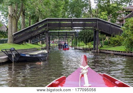 GIETHOORN, NETHERLANDS - AUGUST 9, 2016: Tourists in small boats under the bridges of Giethoorn, The Netherlands