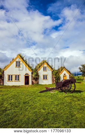 Interesting ethnographic museum Glaumbaer in Iceland. Facade of the farmhouse and ancient rural wheelbarrow. The concept of the historical and cultural tourism