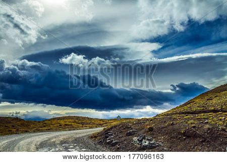 Scary black clouds over the Chilean Patagonia. Dirt road in the National Park Torres del Paine, Chile. The concept of active and extreme tourism