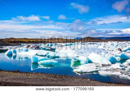 White-blue ice is piled up in turquoise water of the lagoon. Northern nature. The unique nature of Iceland. Drift ice Ice Lagoon - Jokulsarlon. The concept of extreme northern tourism