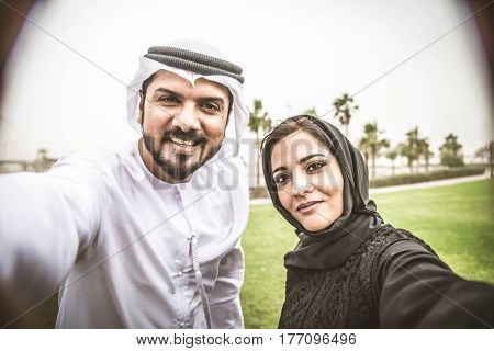 Arabic couple with traditional dress taking selfie