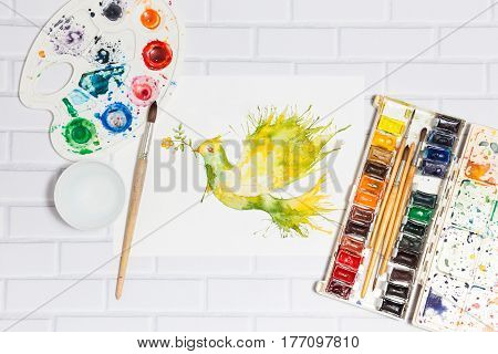 Hand drawn watercolor sketch with green dove flying with flower branch and leaves. Lying flat paints paintbrushes and palette on the white brick background - concept of human creativity top view.