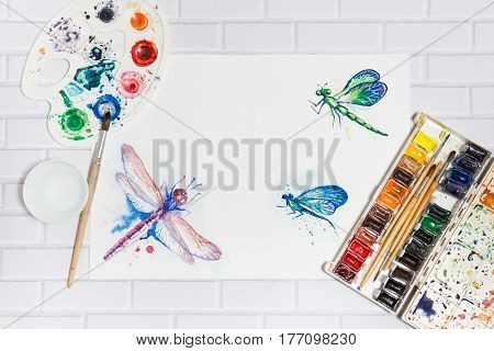 Hand Drawn Bright Sketch of Blue Green and Violet Dragonflies with lying paints paintbrushes and palette on the white brick background - concept of human creativity flat top view