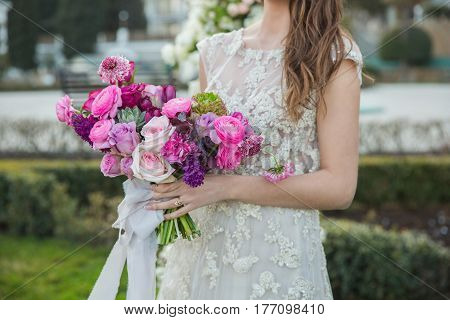 Bride with beautiful wedding bouquet. Pink rose and other flowers.