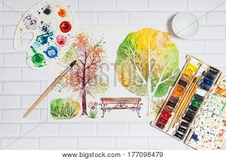 Hand Drawn Bright Sketch with autumn trees bench bush and lying flat paints paintbrushes and palette on the white brick background - concept of human creativity top view
