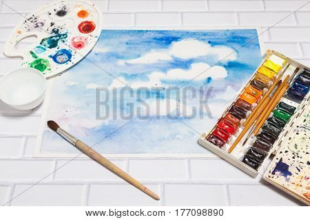 Hand drawn Sketch of Bright Colorful Blue Sky With White Clouds with lying flat paints paintbrushes and palette on the white brick background - tools for drawing top view