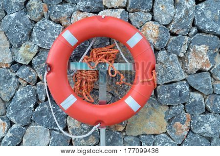 Orange lifebuoy on a stone wall rescue