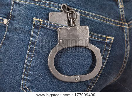 Black metal police handcuffs in the back jeans pocket