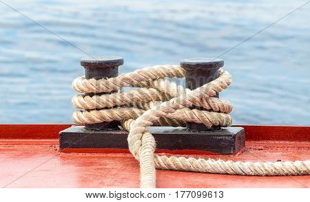 Mooring bollard with a fixed rope on the ship against the water background