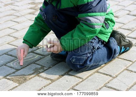 The image of the child in such a cold season sitting on his haunches and draws on asphalt chalk pictures.