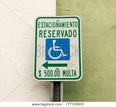 A sign written in spanish that says parking for handicapped only or $500.00 fine