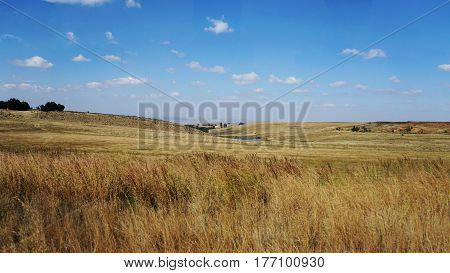 Dry land in South Africa in autumn, brown meadows an fields, blue sky with white clouds