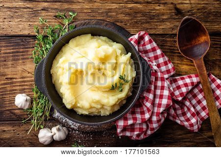 Mashed potatoes boiled puree in cast iron pot on dark wooden rustic background top view