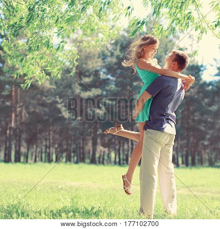 Happy young couple in love enjoys spring day loving man holding on hands his woman carefree walking at park
