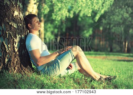 Relaxing man is dreaming under a tree with eyes closed meditating enjoying the warm evening sunset in profile