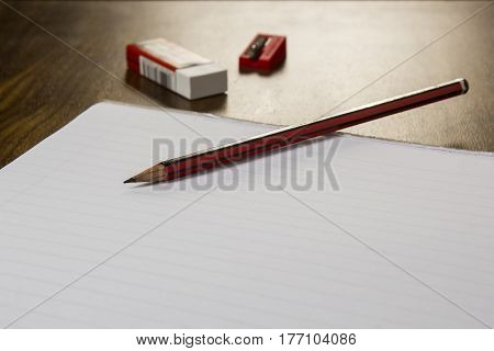 Assorted office utensils including a pencil, eraser, pencil sharpener and a blank paper notebook on a wooden table