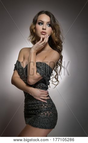 Attractive sexy blonde posing provocatively indoor. Portrait of sensual woman wearing brown fluffy sweater in classic boudoir scene. Woman with long hair and sweater against a white wall