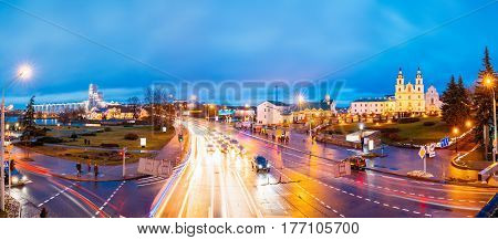 Minsk, Belarus. Panorama With Night Traffic On Illuminated Street And Cathedral Of Holy Spirit In Minsk. Famous And Main Orthodox Church Of Belarus At Evening. Famous Landmark.