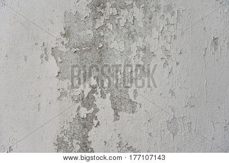 White painted cement wall is dirty, cracked and peeling