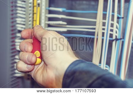 A close-up electrician hand performs electrical work. Screwdriver, electrical terminals for connections, cable connections on a blurred background. Electrical wiring.