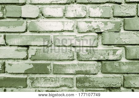 Green old brick wall with exfoliating paint, shabby background
