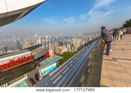 Hong Kong, China - December 7, 2016: The Peak Tower and rooftop restaurant atop Victoria Peak in a sunny day view from observation deck of Peak Galleria. Tourists observe the Victoria Harbour skyline.