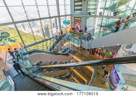 Hong Kong, China - December 10, 2016: People on escalators of shopping mall Peak Tower, landmark and icon of Hong Kong. On background Victoria Harbour cityscape on sunny day.