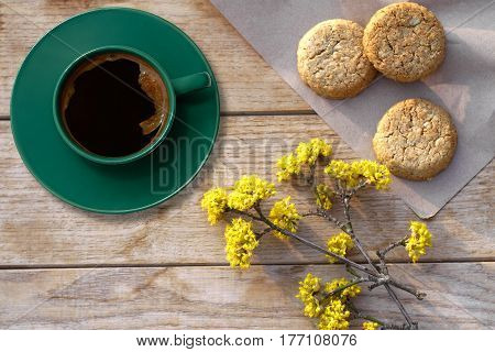 Arrangement of a coffee in a green cup with biscuits on a table with a spring blossoms-top view