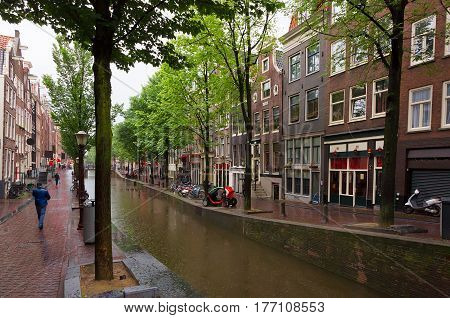 Red light district in Amsterdam on a rainy summer day. Capital of Netherlands. View of the canal with an old building. Horizontal Image