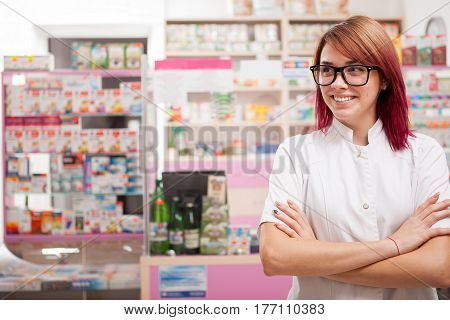Smiling Pharmacist In Glasses In Front Of Her Desk