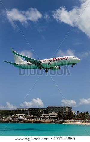MAHO  BAY BEACH - AUGUST 1:  Aeroplane Caribbean Airlines is landing on Princess Juliana International Airport, over Maho Bay Beach seen in St.Martin/St.Maarten on August 1, 2015