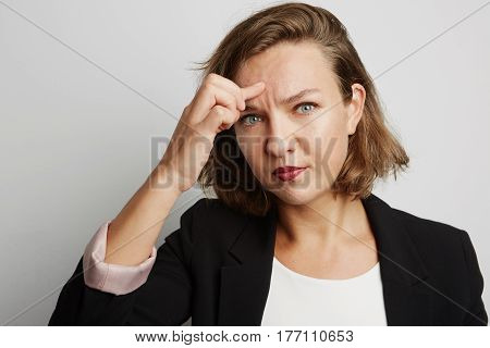 Close up portrait of young business woman made a mistake, studio photo isolated on a white background.