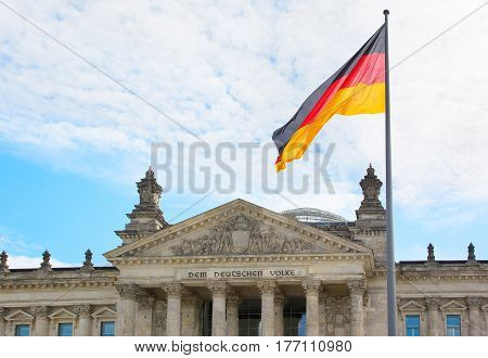 Waving German flag closeup over the Reichstag Parliament building of Berlin. Germany
