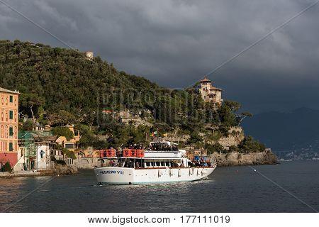 PORTOFINO, ITALY - DECEMBER 2016: Excursion boat at the stormy bay of Portofino town, Italy