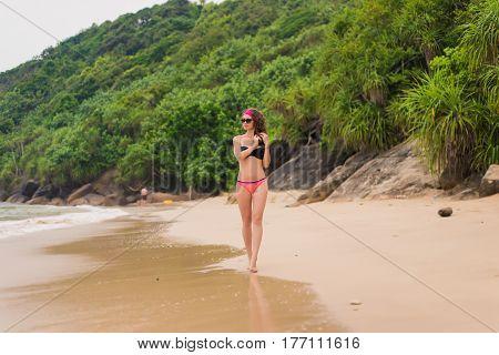 young beautiful woman in bikini on blue ocean background. Woman in bikini at tropical beach. woman in hat on the beach