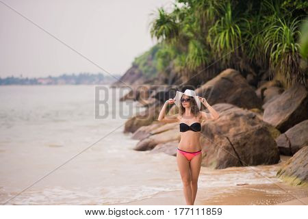 Elegant woman with long hair in a bikini relaxing on the beach. Summer Vacation. Nature over Sea Background.