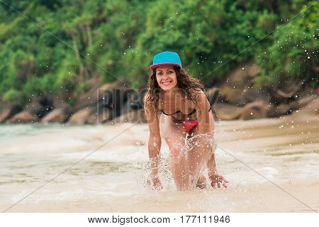 Curly girl walking the summer beach.Young woman having fun on the beach