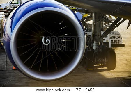 an airplane turbine detail with wing and undercarriage on the background