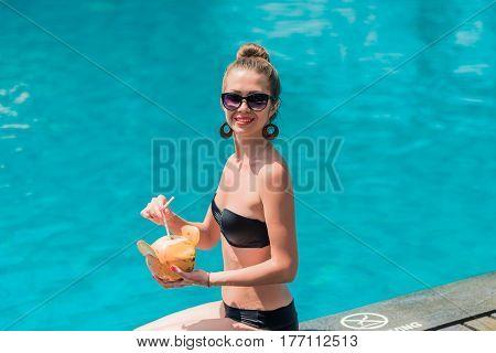 Happy girl in bikini seat near swimming pool with coconut. Woman sunbathing in bikini at tropical resort. Outdoor summer portrait of sexy girl