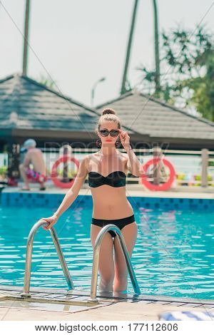 Sexy beautiful woman getting out of a swimming pool. Summer portrait of sexy girl in sunglass outdoor. Tanned female model posing by blue pool water.