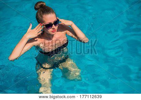 Sexy woman in bikini enjoying summer sun and tanning during holidays in pool . Top view. Woman in swimming pool.