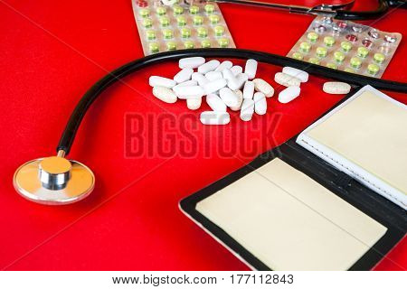 Pills tablets and stethoscope on red background. Pharmaceutical medicament cure in container for health. Antibiotic painkiller closeup. Copy space for text.