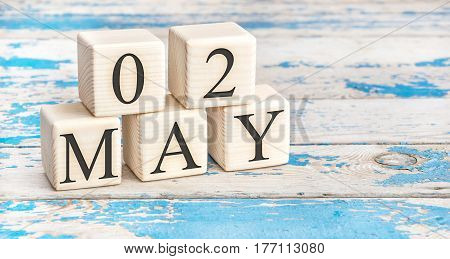 May 2nd. Wooden cubes with date of 2 May on old blue wooden background.
