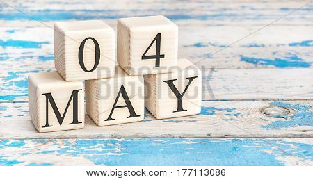 May 4th. Wooden cubes with date of 4 May on old blue wooden background.