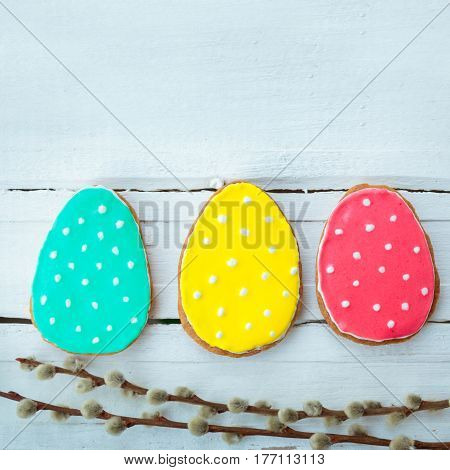 Happy easter. Easter background. Easter cookies. Gingerbread in the form of colored Easter eggs and willow branches on a background of white wooden desk. Free space