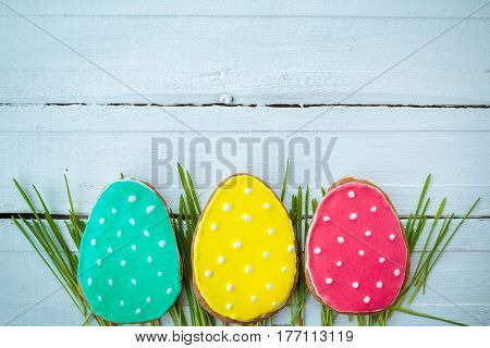 Happy easter. Easter background. Easter cookies. Gingerbread in the form of colored Easter eggs on green grass on a background of white wooden desk. Free space