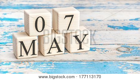 May 7th. Wooden cubes with date of 7 May on old blue wooden background.