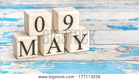 May 9th. Wooden cubes with date of 9 May on old blue wooden background.