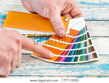 Man's hands choosing color from colour swatches book.