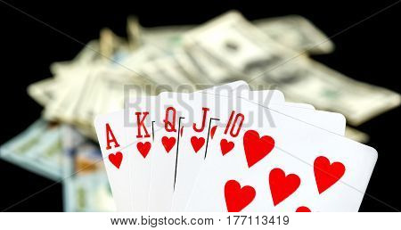 Combination of playing card on dollar background.